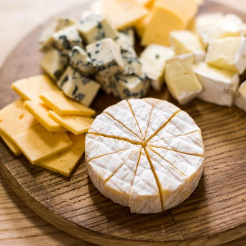 Assortment of cheeses placed on a wooden board.